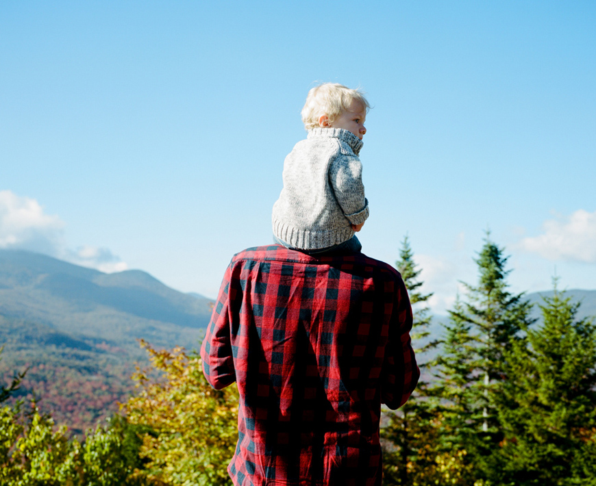 rich and beautiful film image of son on dad's shoulders in red flannel overlooking mountains by ash imagery