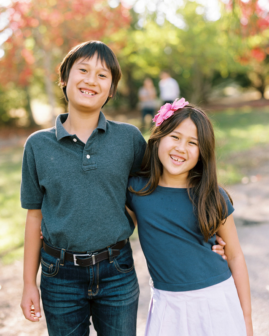 backlit natural light photo of sister and brother in navy blue shirts by photographer kimberli moffitt-tsui