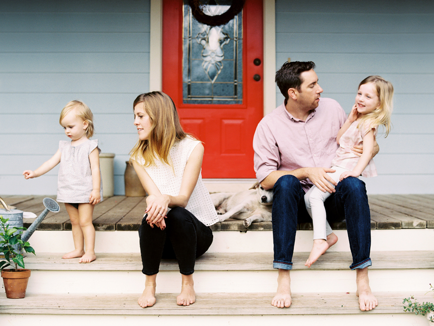 cute austin family sitting on porch in front of red door by heather moore
