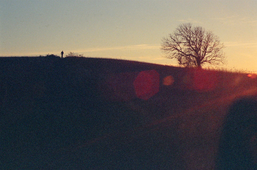 film image of man very small with sun flare at sunset by photographer danielle gardner