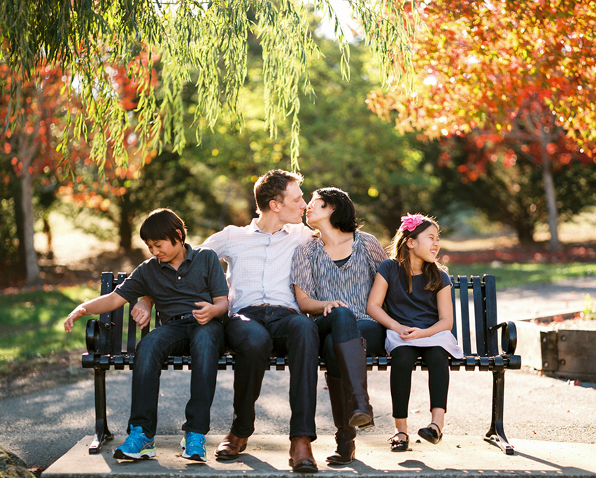 funny color film image of parents kissing while kids look away by photographer kimberli moffitt-tsui