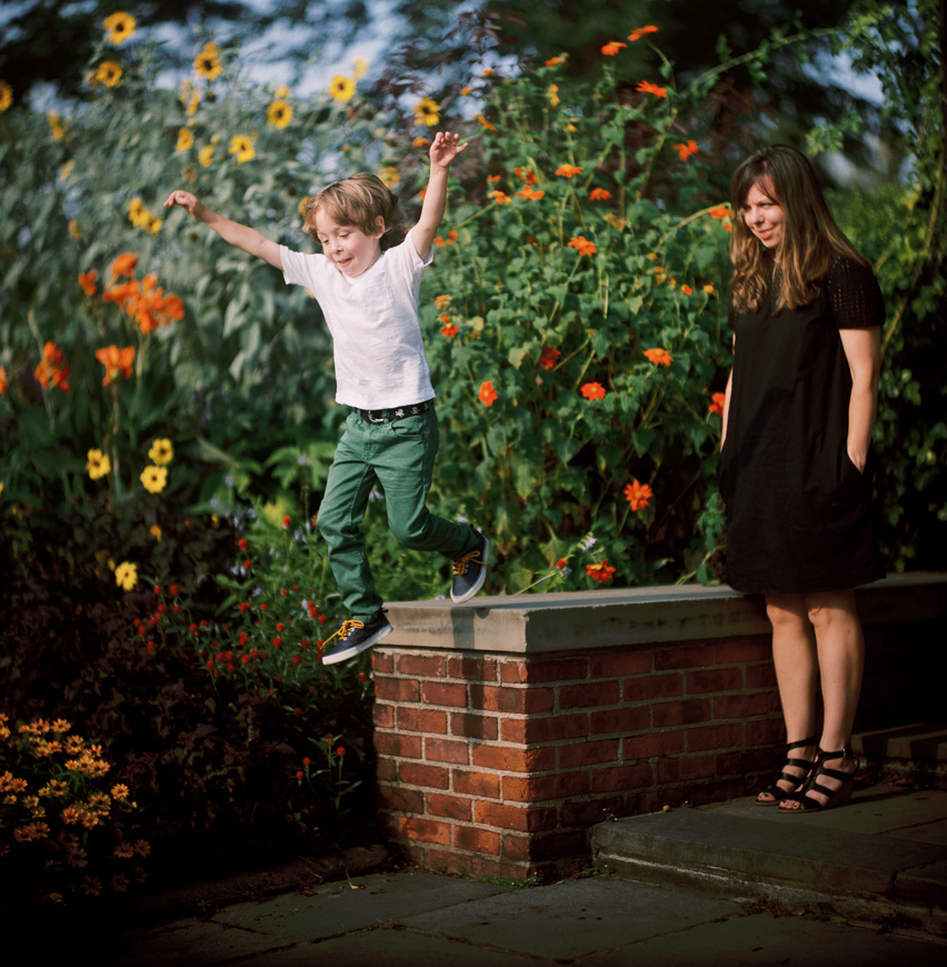 little boy in green jeans jumping in front of orange flowers by photographer zalmy b