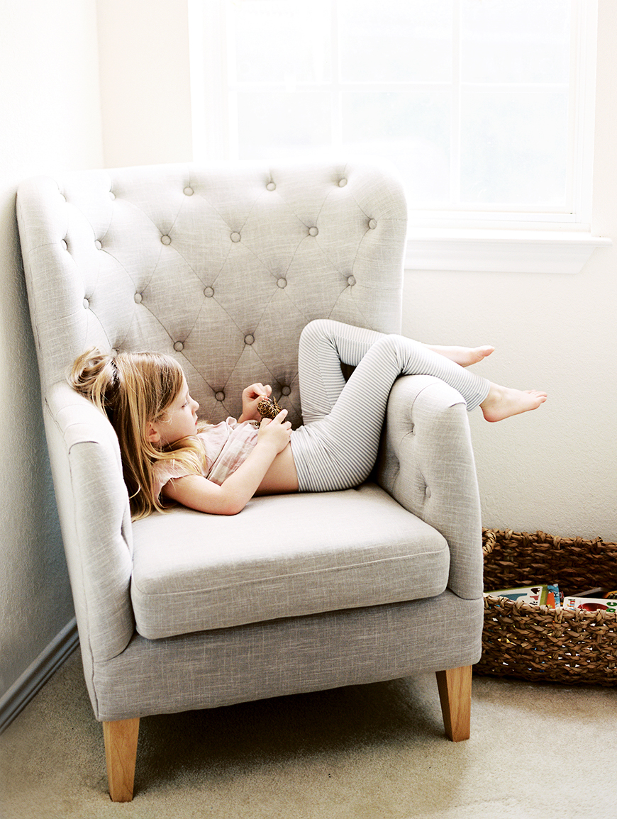 little girl in chair sitting sideways in striped leggings by texas photographer heather moore