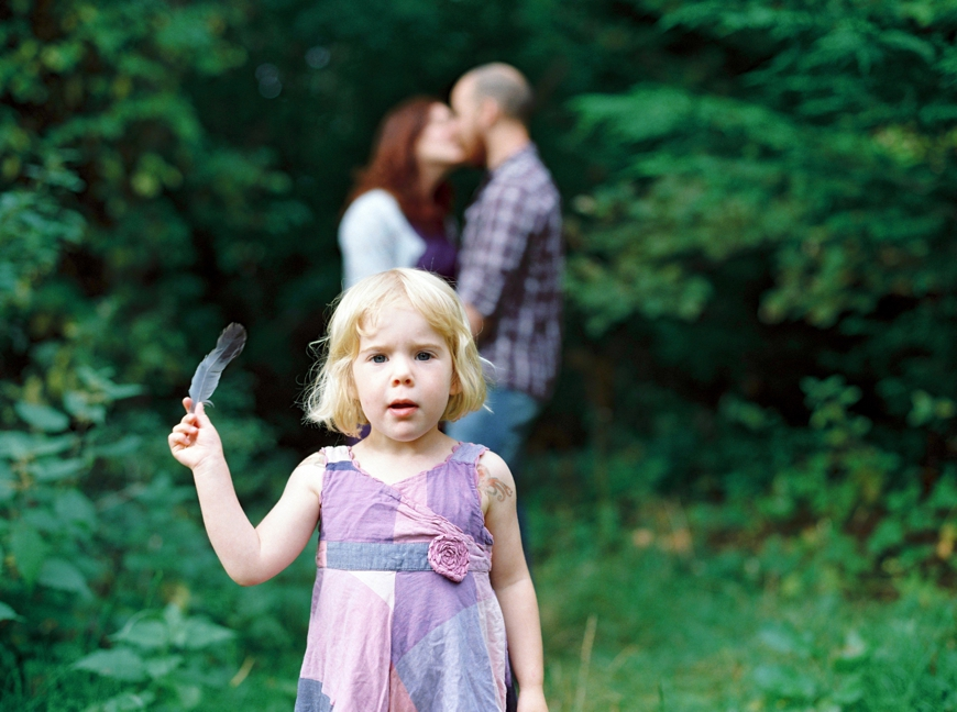 little girl in purple holding a feather in front of parents by photographer molly matcham