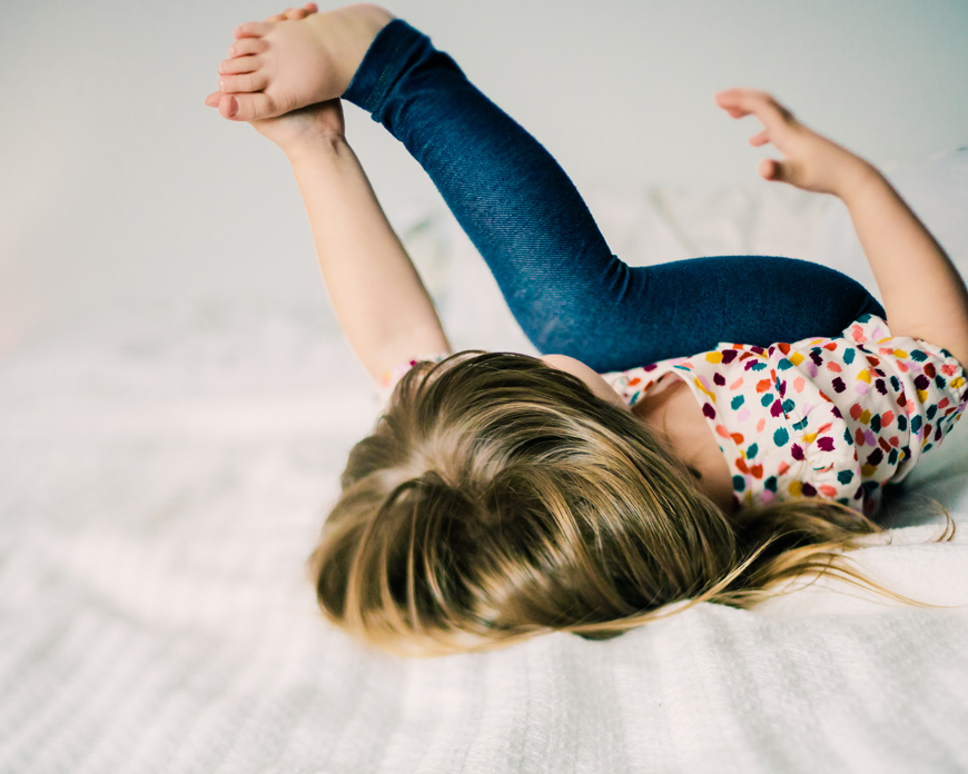 little girl on bed in dotted dress rolling on bed by photographer kate de la rosa