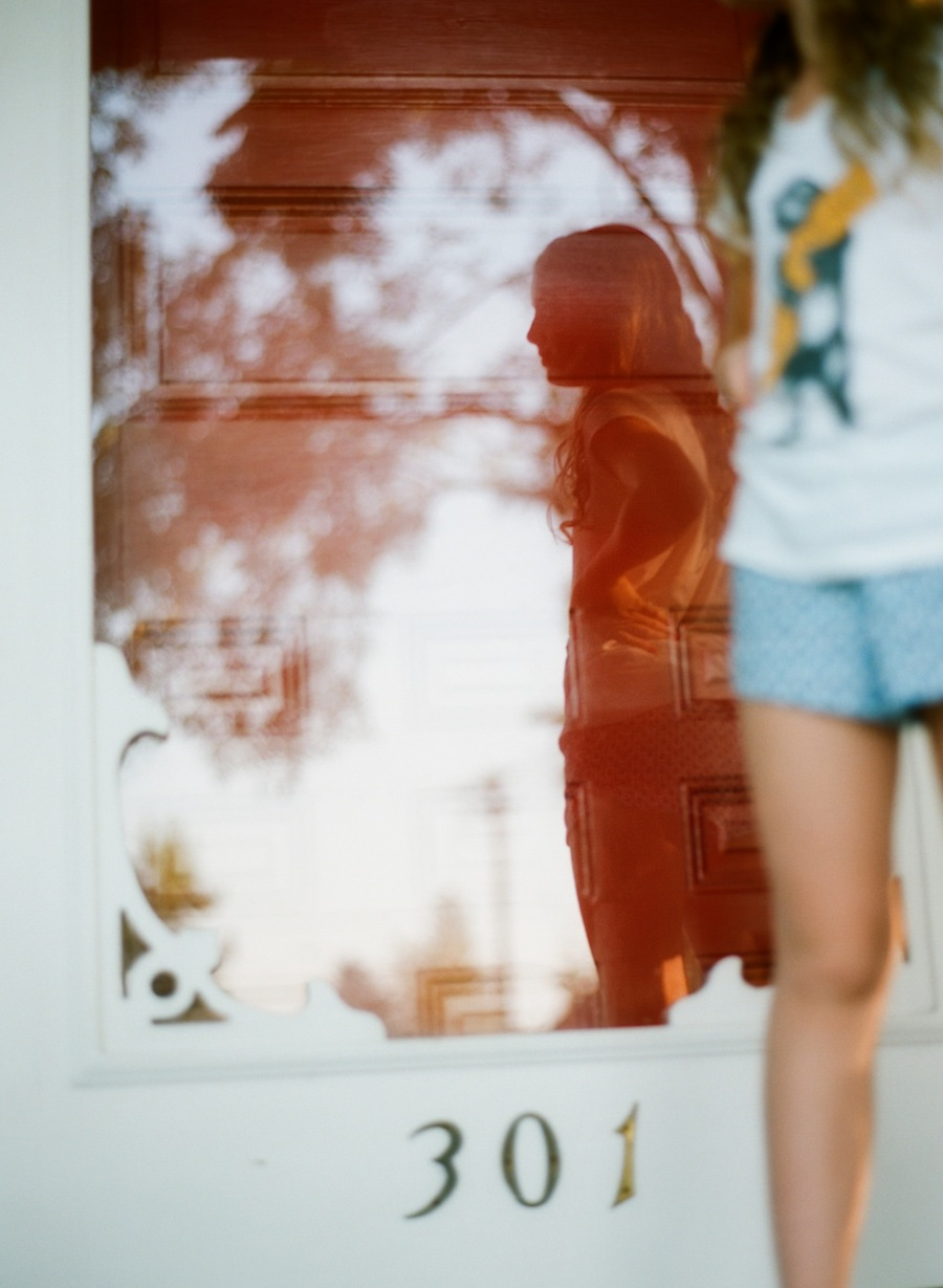 lovely film image of girl standing in front of house she grew up in by photographer amy grace