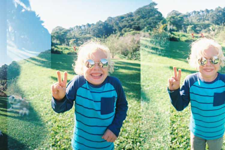 maui photographer wendy laurel's double exposure on film of little boy in mirrored sunglasses with peace sign