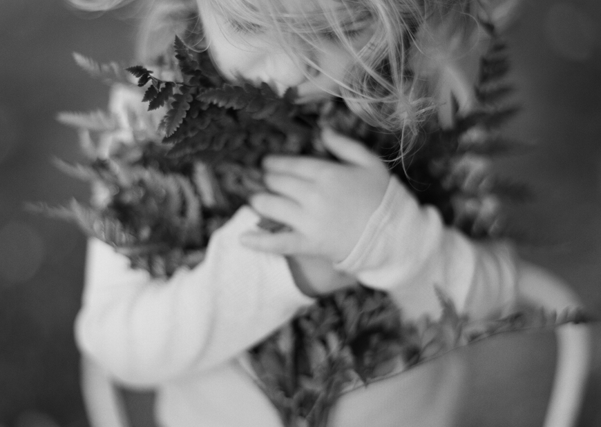 photographer amanda brubaker 's black and white film image of little girl holding ferns