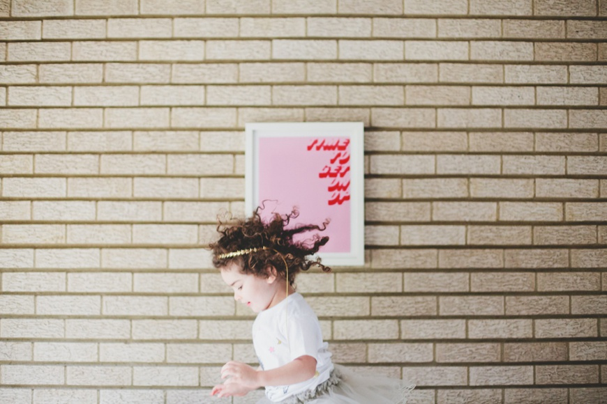 photographer kelly christine image of little girl with curly hair running by wall with pink framed poster
