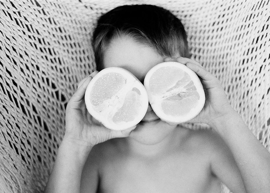 photographer samara wheeldon's image of little boy in hammock with oranges covering his eyes