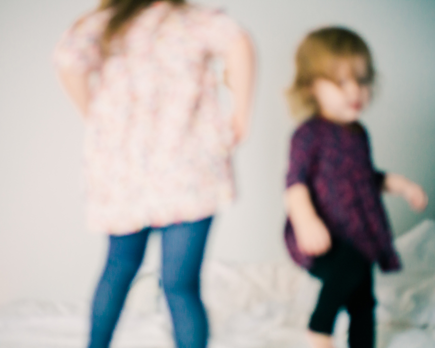 two sisters blurred jumping on bed