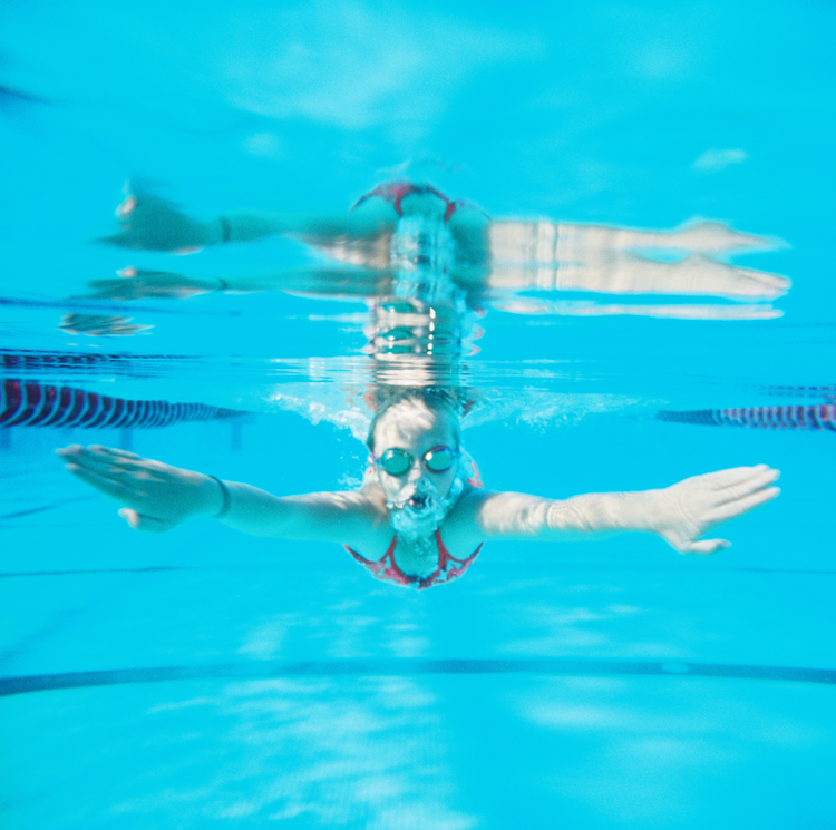 underwater film image of girl doing breaststroke by maui photographer wendy laurel