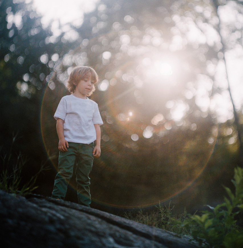 zalmy b's film photograph of boy with sunflare