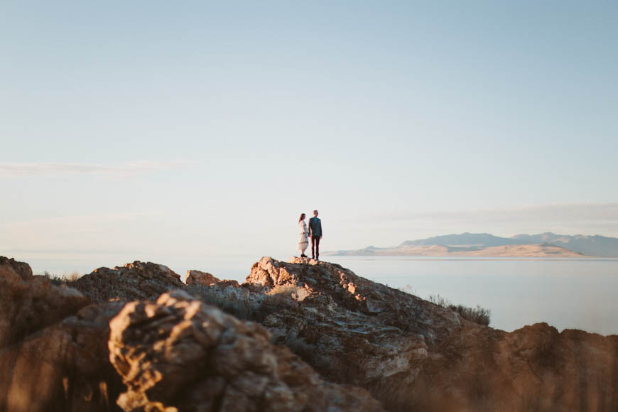 couple up on mountain with lots of sky by utah photographer kandice breinholt photography