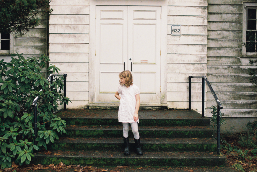 film image of girl in white dress and black boots in front of white house by photographer emily mccann