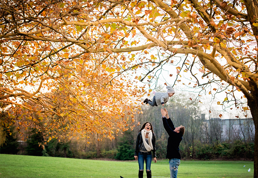 laughing family in fall leaves with kid in air by photographer sarahjanemphotography