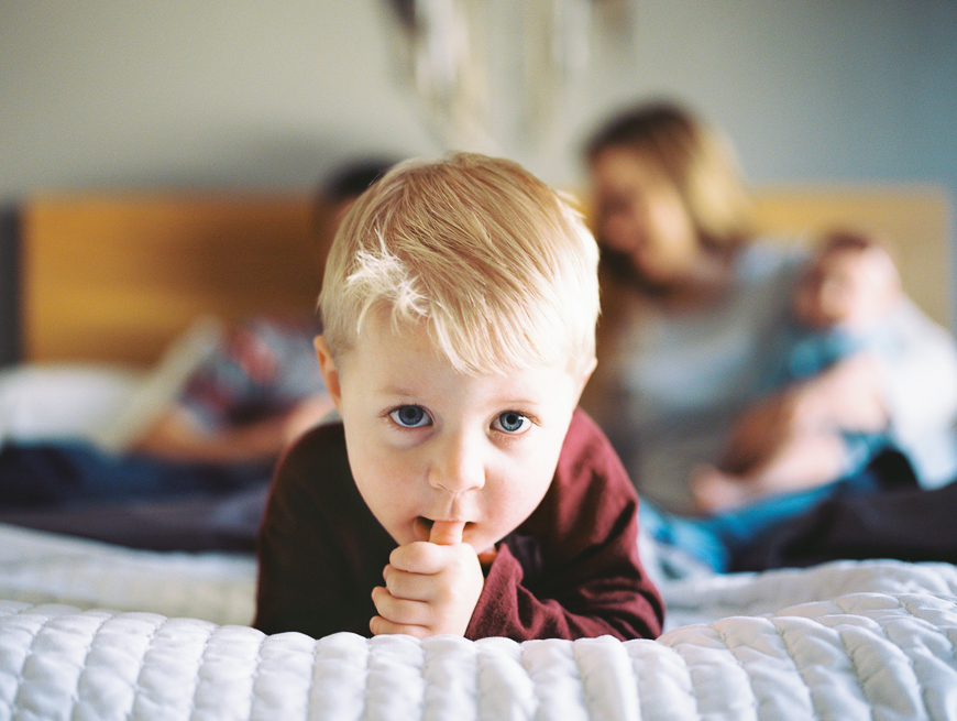 little boy with thumb in his mouth on bed with parents behind him by photographer samantha kelly