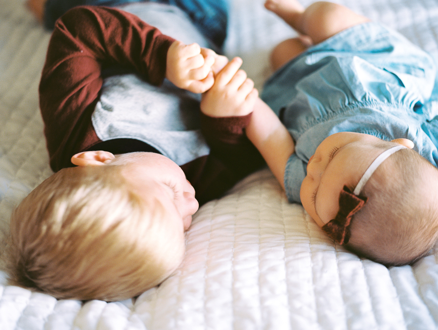 little brother and baby holding hands on bed by samantha kelly photography