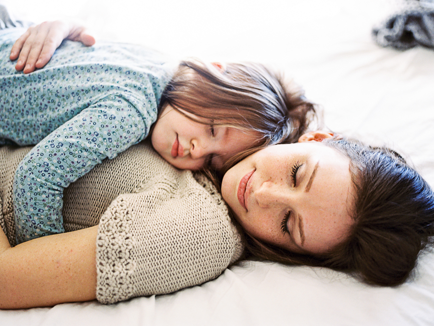 mom and daughter laying close with eyes closed on white bed photograph