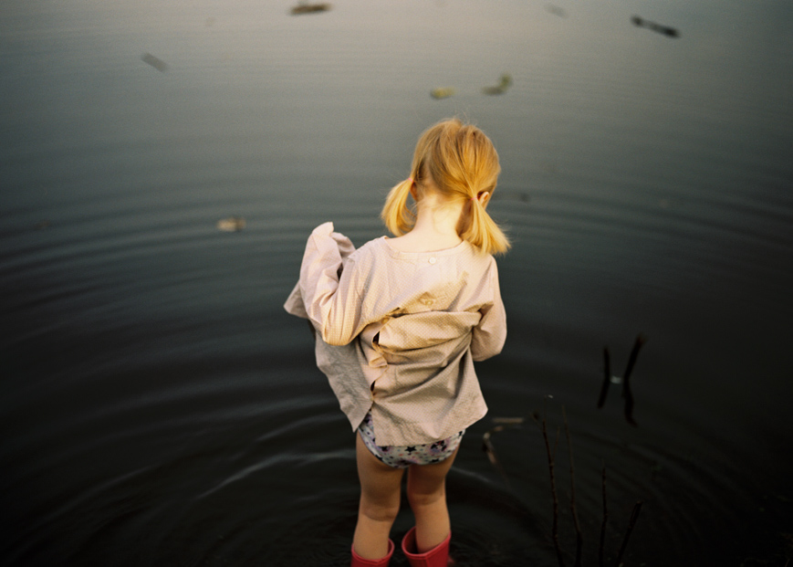 photographer amanda voelker's image of little girl in pond water in dress