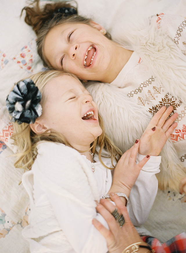 two girls laughing on bed by photographers laurelle plus dale
