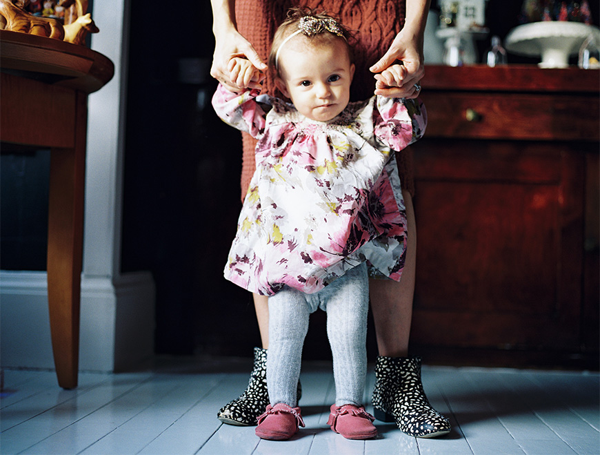 baby girl in tights standing with hands held by mom is cool ankle boots image by brooke schultz