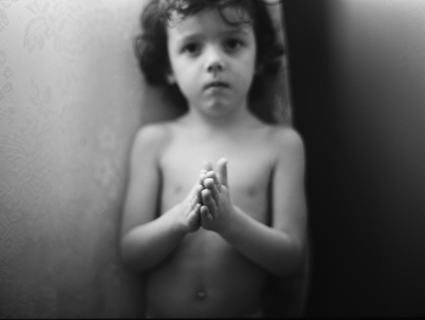 black and white image of boy with praying hands by the paper deer photography