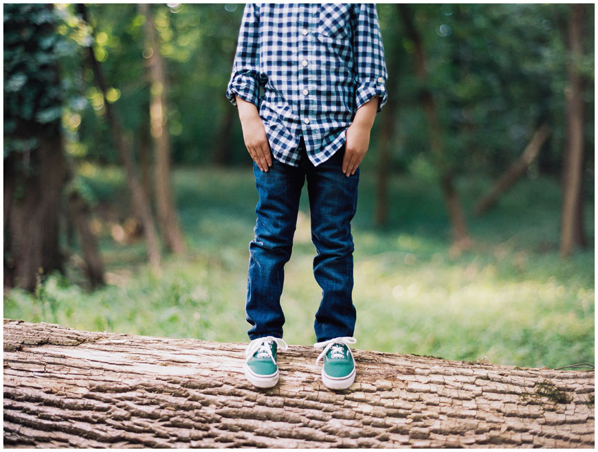 boy in blue checked shirt standing on log image by photographer cindy lee