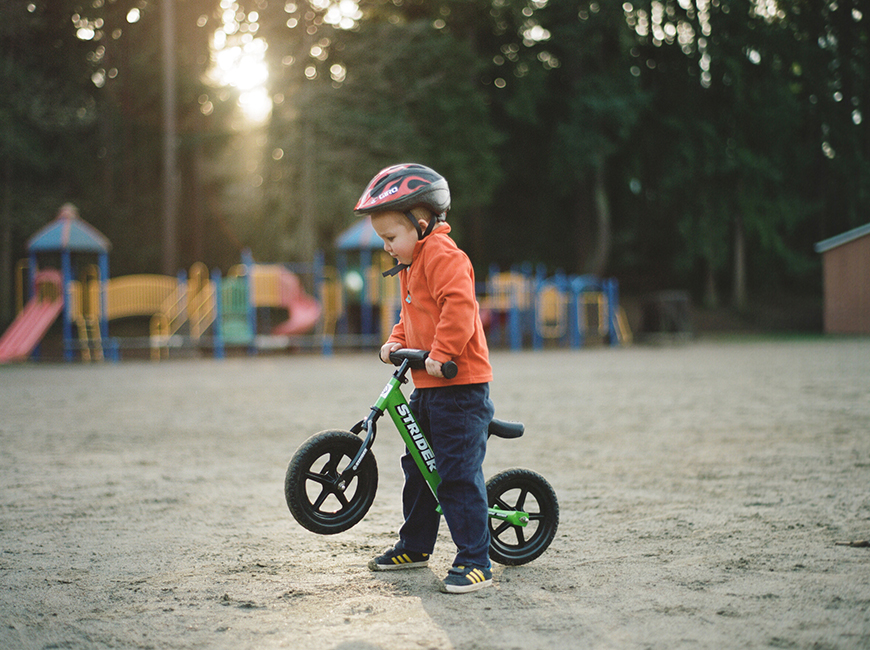 boy on bike with natural light at playground by heidi leonard