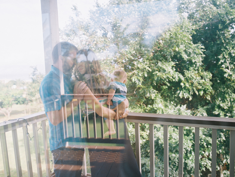 family photo through window in maui by maui family photographer wendy laurel