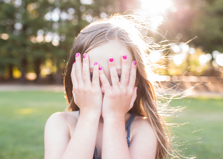 image by anna dobrenski of girl with pink nails covering her face