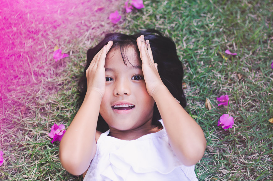 image of girl on ground with pink flowers by kim ebert photography