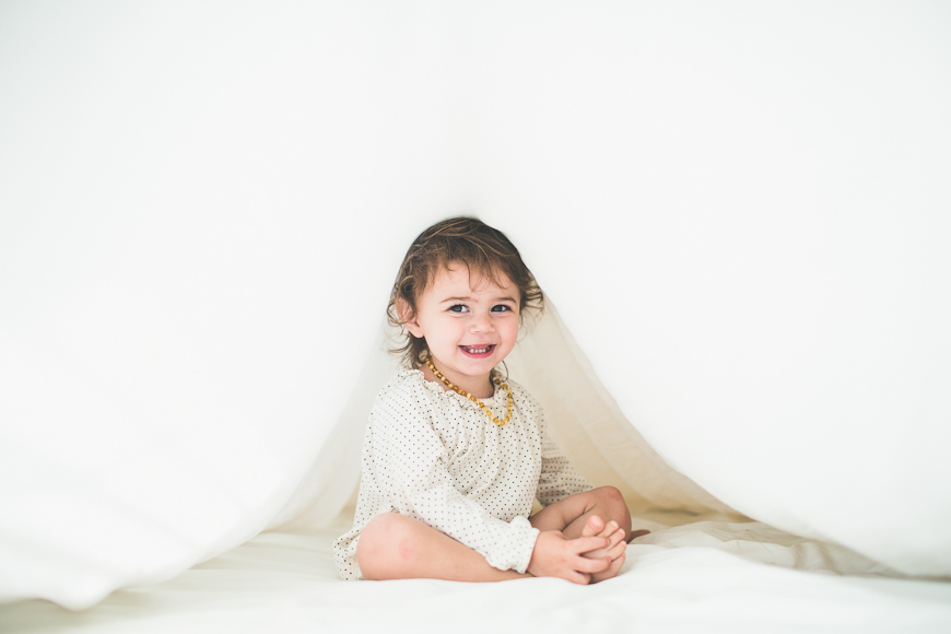 kym vitar photography's portrait of child on white bed with sheet covering her