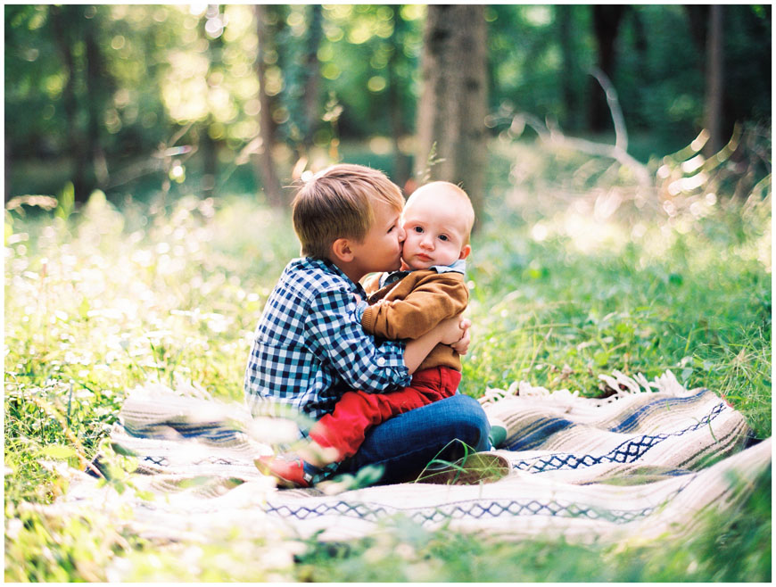 little boy in brothers lap in field image by cindy lee
