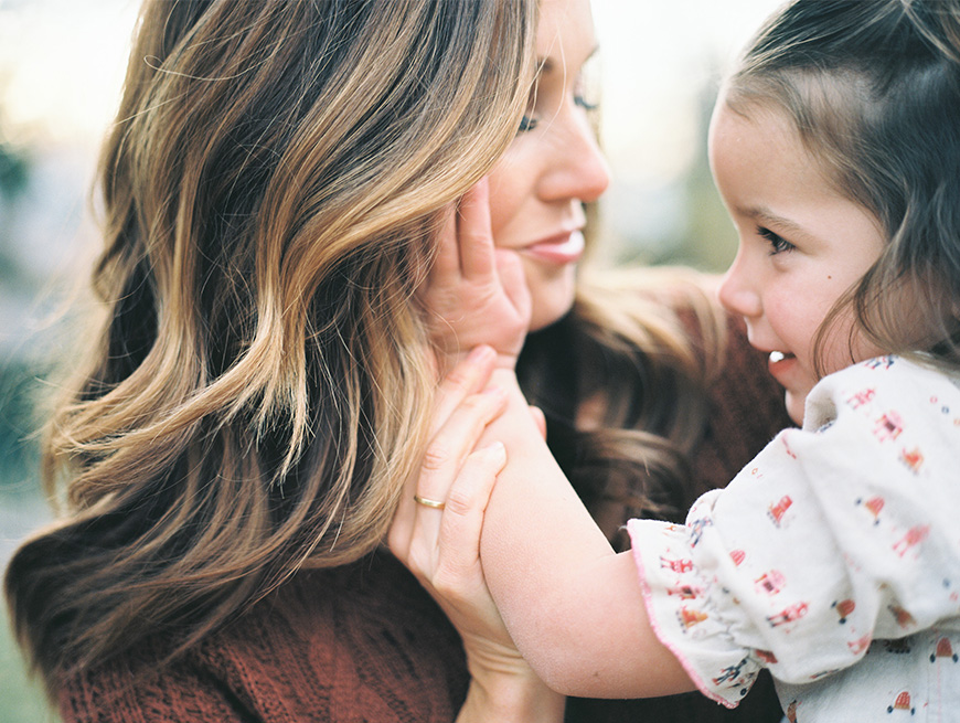 little girl with hand on moms face image by photographer brooke schultz