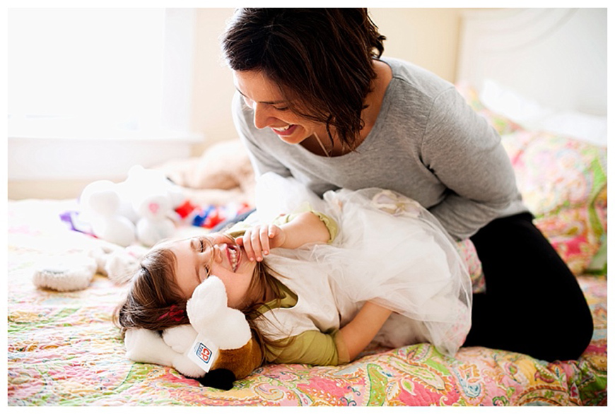 penny gray photo's image of daughter giggling with mom on flowered bed