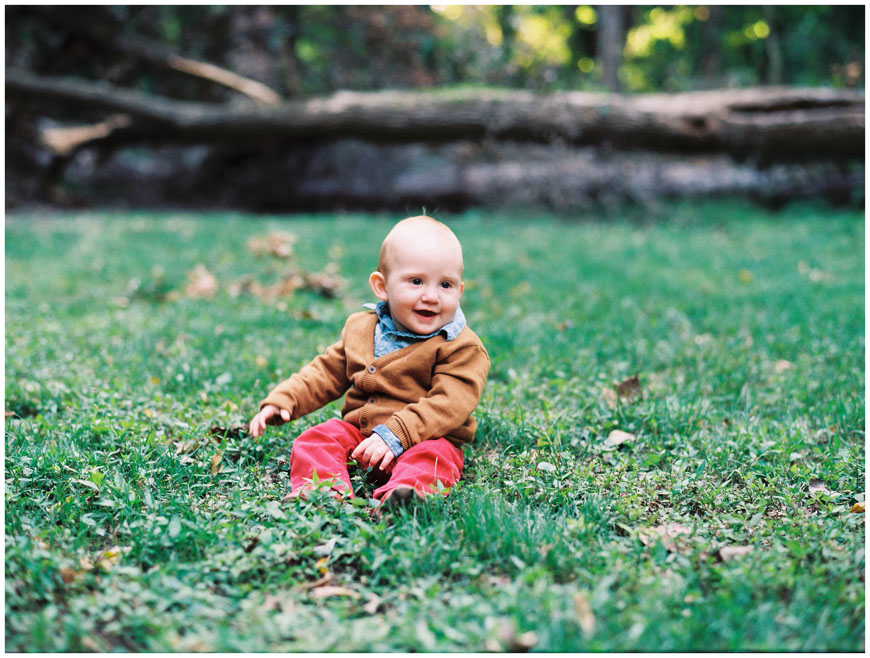 smiling baby in red pants in field with natural light on film