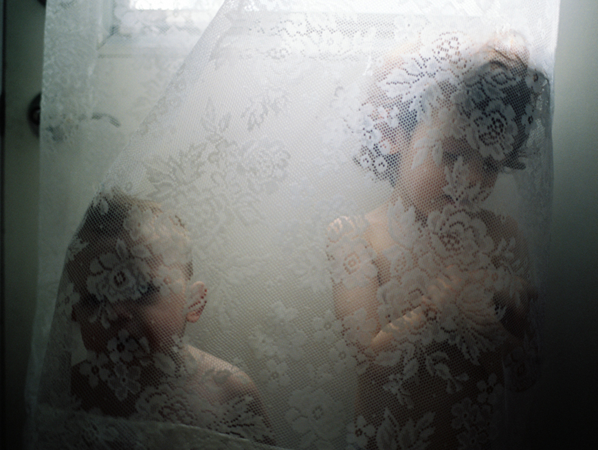 two boys behind white lace curtain image