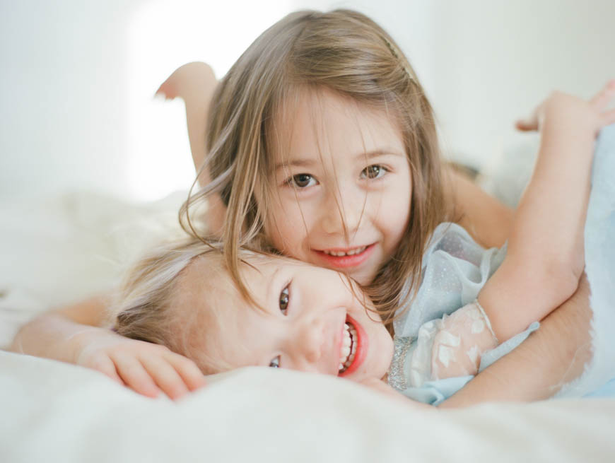 two girls hugging on white bed image