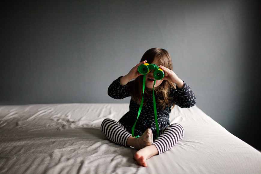 crystal hardin's image of little girl in striped leggins wtih bionaculars on bed