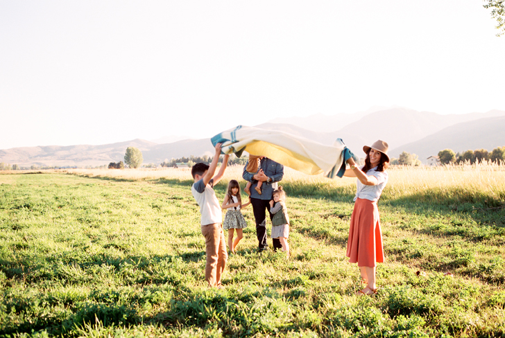 family setting out picnic in green grass by green apple photography