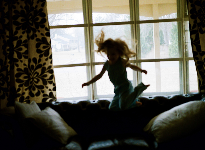 girl jumping on couch in front of windows