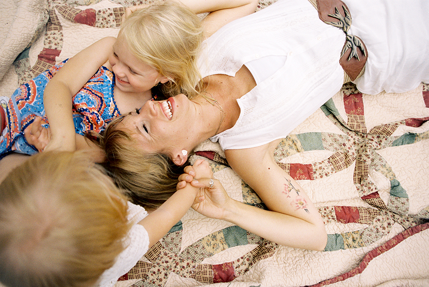 image by amy rae photography of mom on bed with two kids laughing