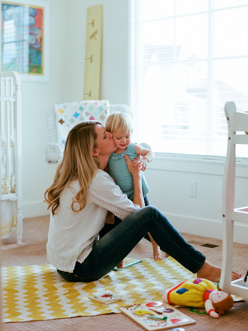 image by carolee beckham of mom kissing toddler in nursery bedroom