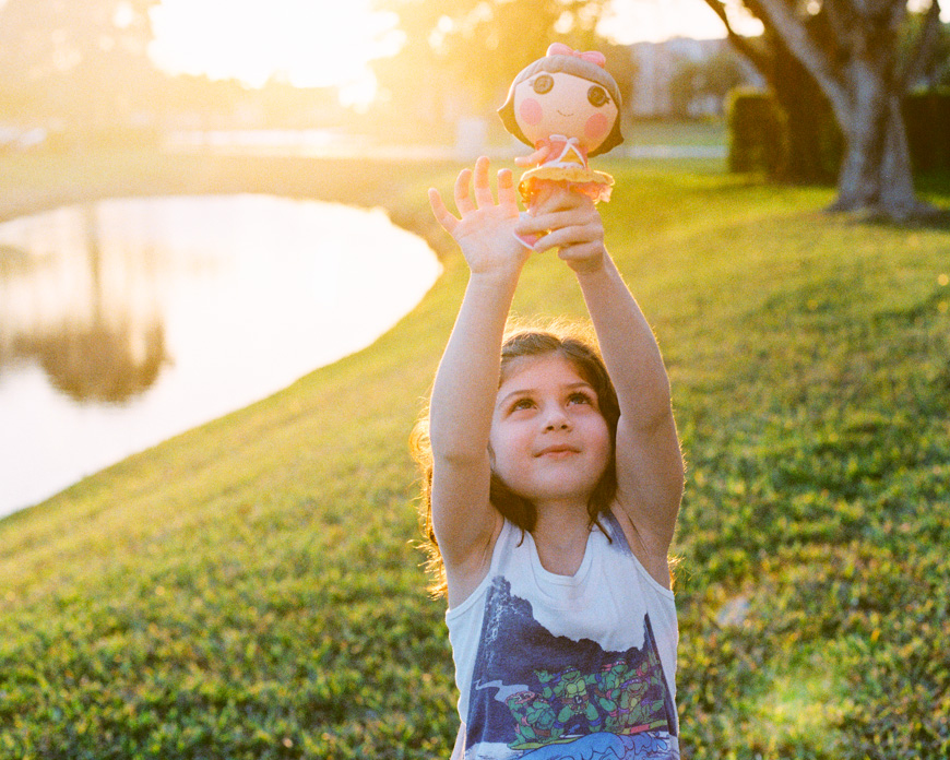 image by jacqueline tobman of little girl holding up toy in sunset light on film