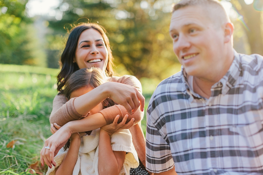 image by lacey monroe of family laughing in green grass
