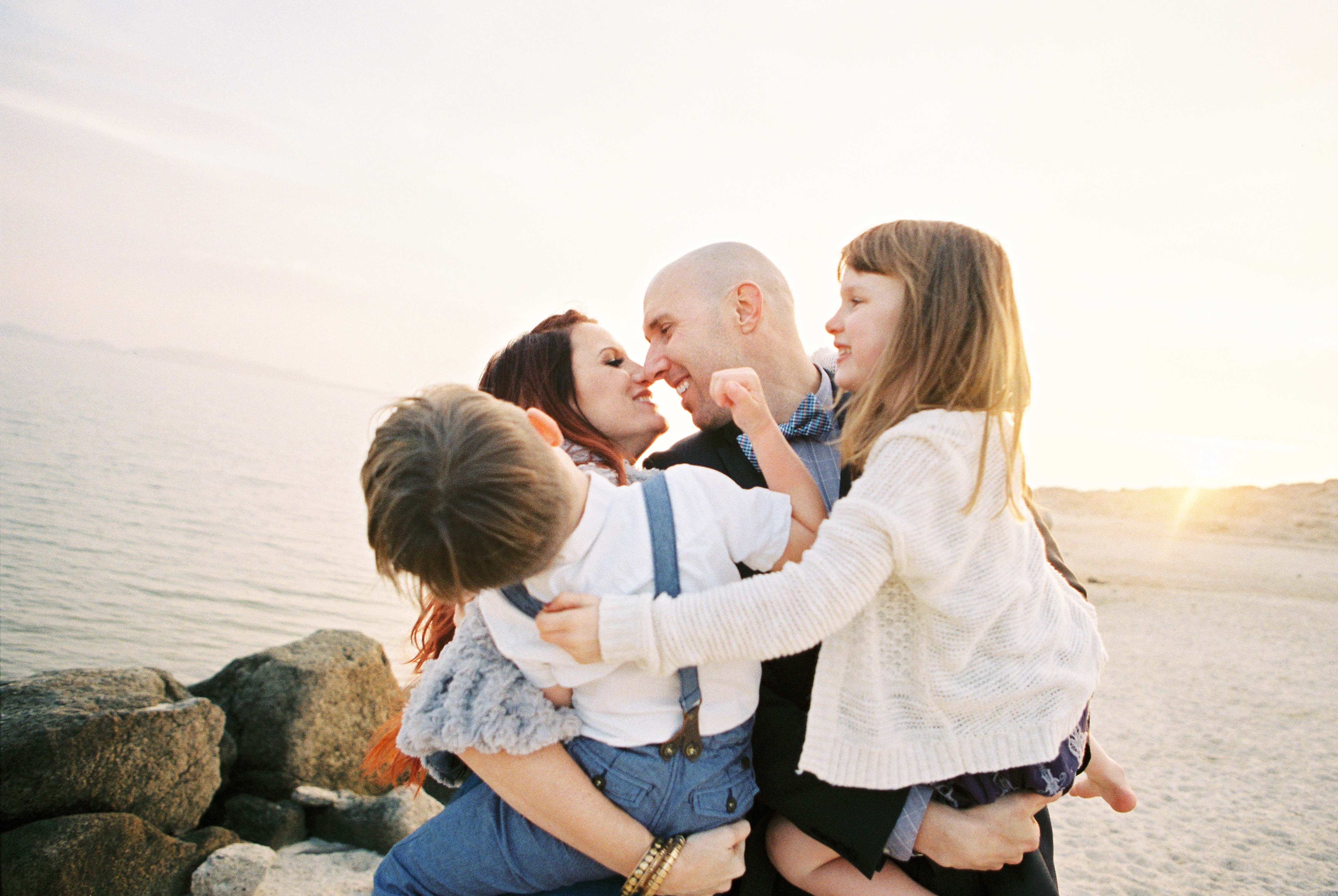 image by yan photo of family kissing and holding kids at sunset