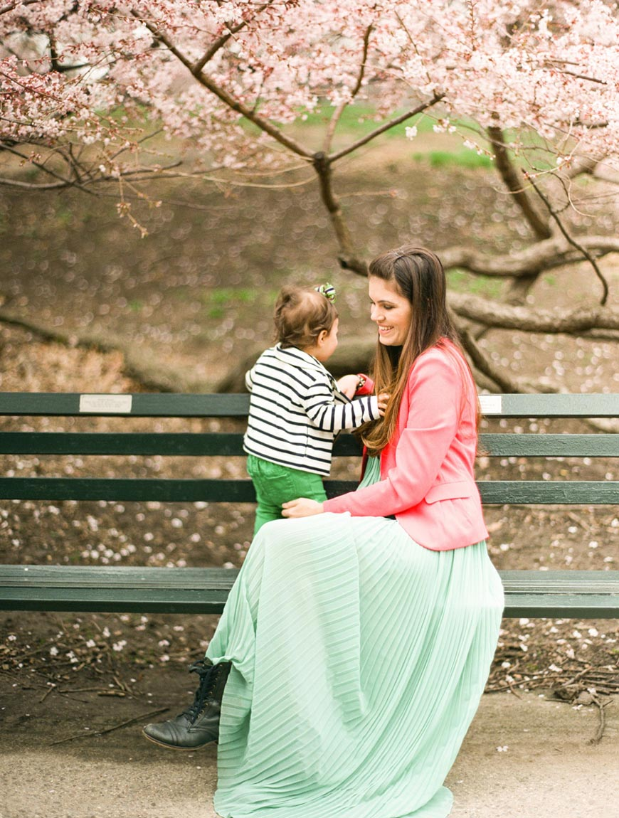 image of mom in green skirt and pink jacket on bench with toddler by photographer lindsay madden