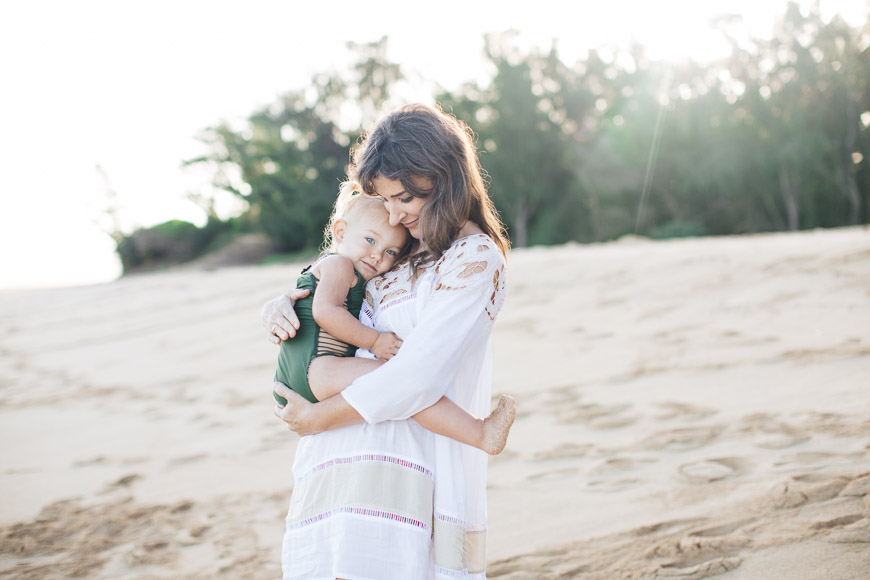 image of mom in white holding little girl in swim suit on beach on maui with sun by cadencia photography