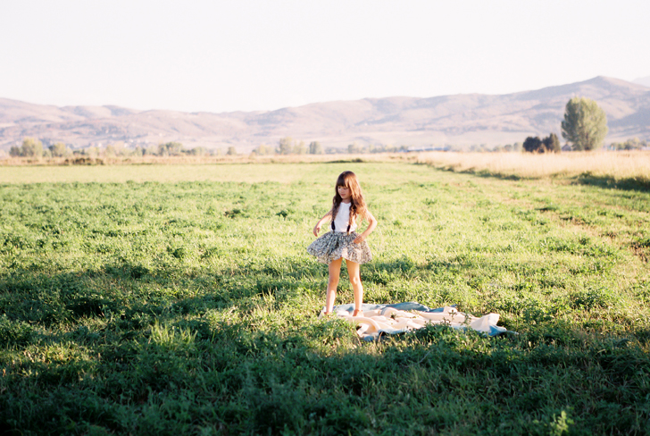 little girl in black and white skirt on green field image